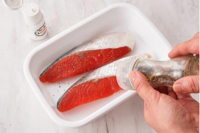 鮭に塩コショウをする