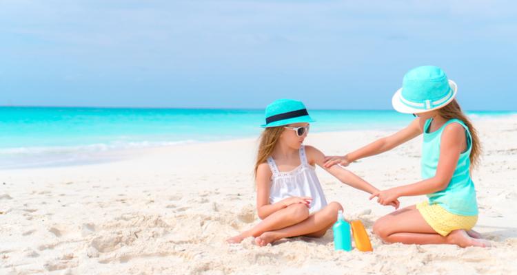 砂浜で日焼け止めを塗る少女と女性