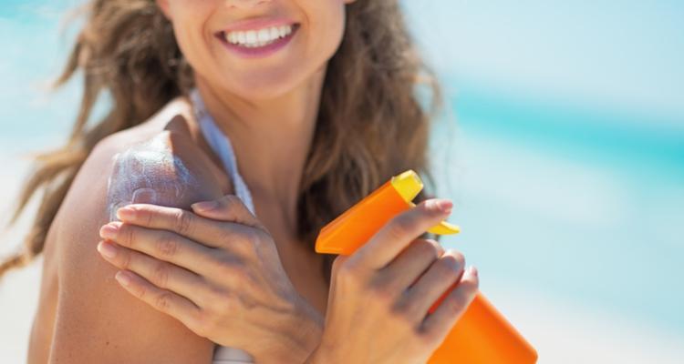 日焼け止めを手に持つ女性
