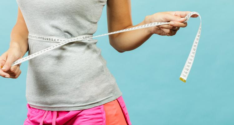 体をメジャーで測る女性
