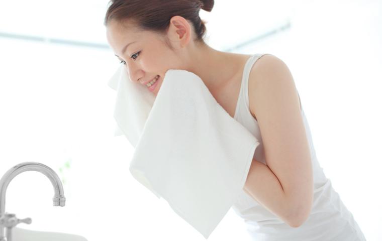 顔をタオルで拭く女性