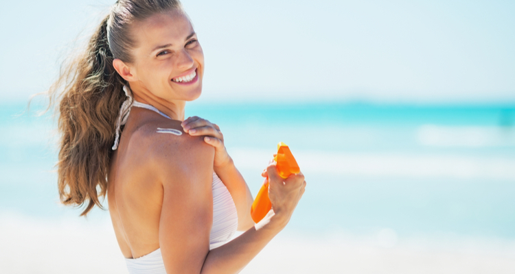 笑顔で日焼け止めを塗る女性